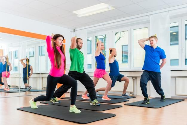 Les hommes et les femmes dans la salle de sport faisant de l'entraînement de pilates