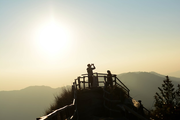 Hommes et femmes debout au sommet de la colline prenant des photos