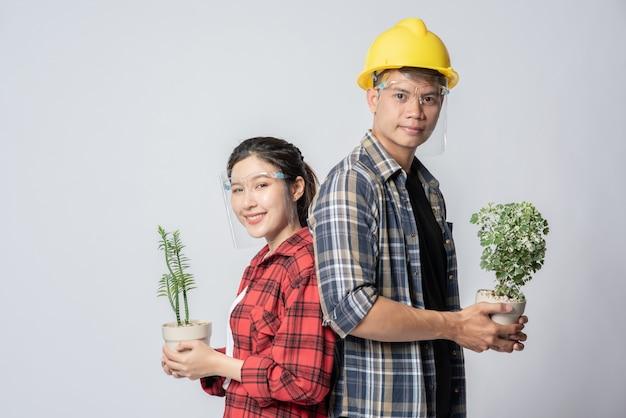 Hommes et femmes debout et tenant des pots de fleurs dans la maison