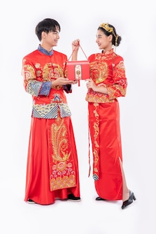 Hommes et femmes portant cheongsam debout avec des sacs rouges