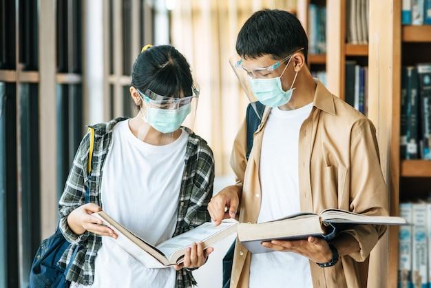 Des hommes et des femmes portant des masques se lèvent et lisent dans la bibliothèque.