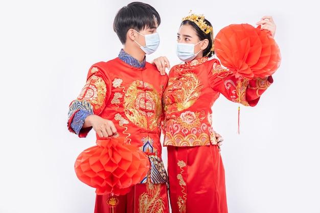 Les hommes et les femmes portant qipao et portant des masques faciaux se tiennent avec une lampe en nid d'abeille