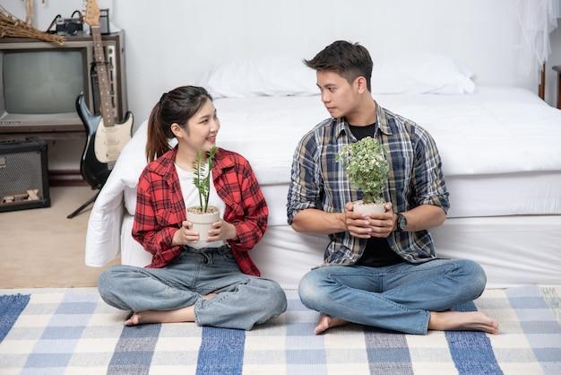 Les hommes et les femmes s'assoient et tiennent des pots de fleurs dans la maison.