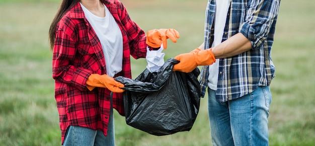 Les hommes et les femmes s'entraident pour ramasser les ordures.