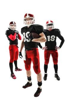 Hommes de fitness caucasiens comme joueurs de football américain posant sur toute la longueur avec un ballon sur fond blanc