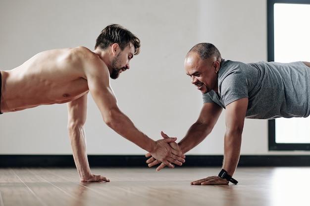 Des hommes forts se donnent cinq coups lorsqu'ils se tiennent en position de planche sur le sol du gymnase