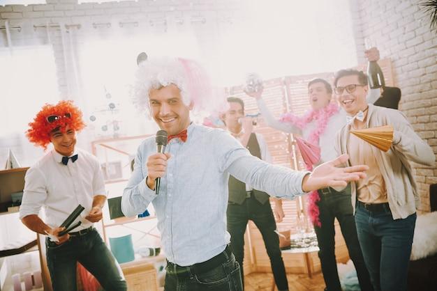 Hommes gais en vêtements colorés chantant karaoké à la fête.