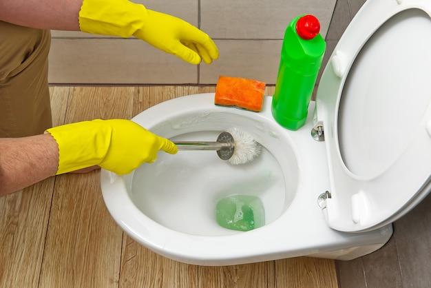 Hommes en gants jaunes nettoyant le concept de nettoyage à domicile de la cuvette des toilettes