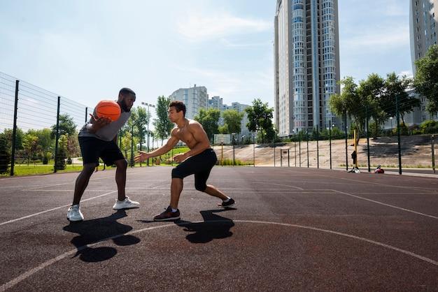 Hommes de grande taille jouant au basket urbain