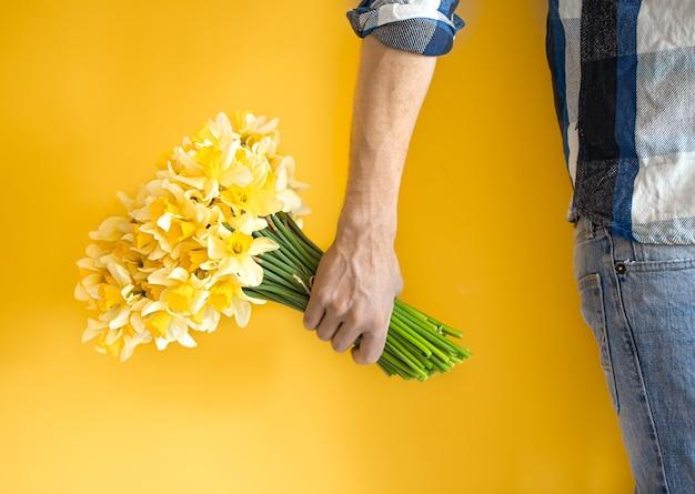 Des hommes en jeans et une chemise tenant un grand bouquet de jonquilles. concept de la journée de la femme et félicitations.