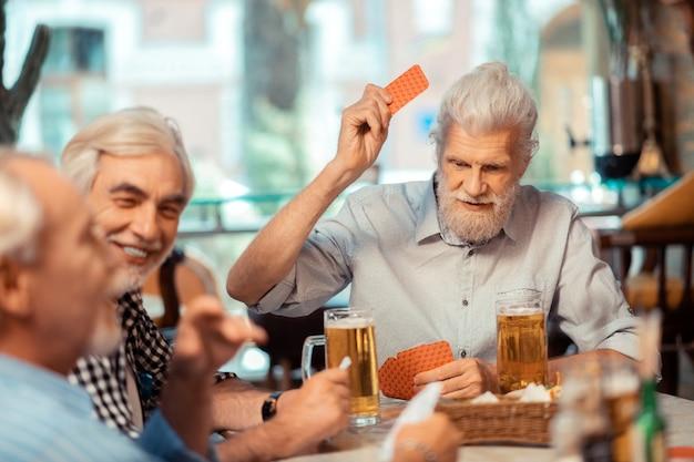 Hommes jouant. hommes retraités aux cheveux gris jouant en buvant de la bière au pub