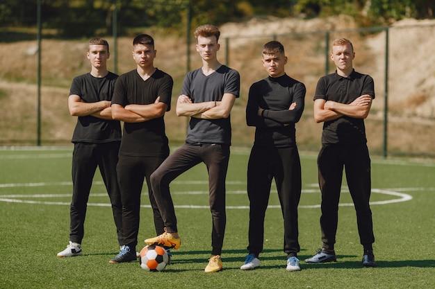 Les hommes jouent au socer au parc. tournoi sur mini-footbal. guy en tenue de sport noire.