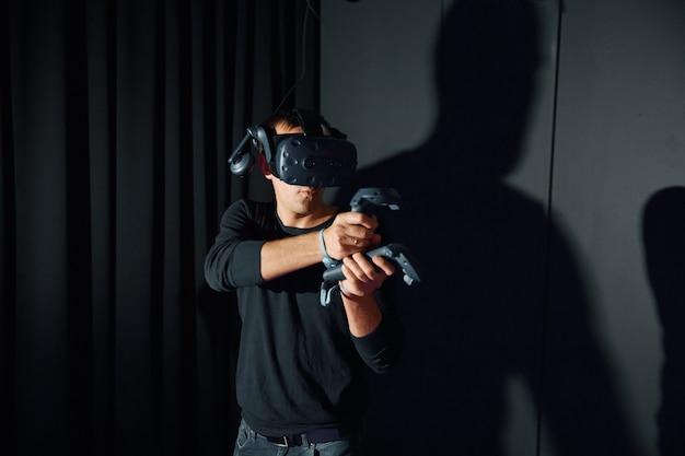 Les hommes jouent avec des lunettes de réalité virtuelle, tient le contrôleur dans ses mains