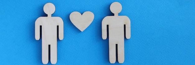 Hommes de jouet en bois et coeur se trouvant sur le fond bleu