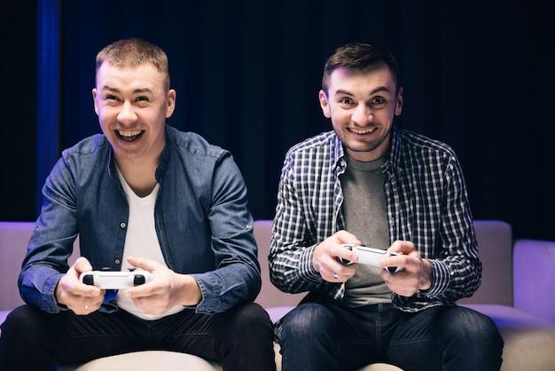 Hommes, joueurs, tenue, contrôleurs, jouer, jeu vidéo