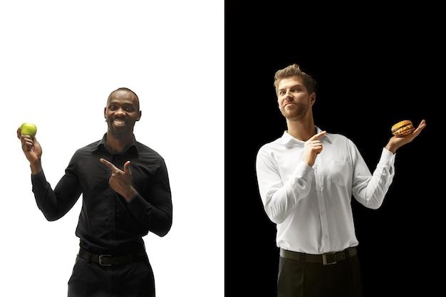 Hommes mangeant un hamburger et des fruits frais sur un fond noir et blanc. les hommes afro et caucasiens heureux. le hamburger, le concept de nourriture rapide, saine et malsaine
