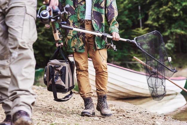 Hommes marchant et portant du matériel de pêche