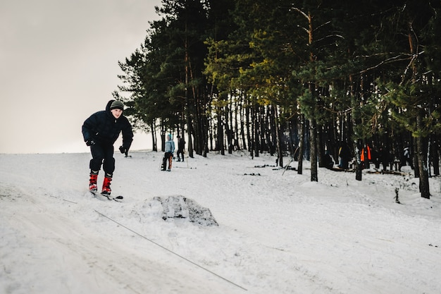 Les hommes montent sur des sauts de ski depuis une colline à partir d'un tremplin de saut à ski sur la neige dans les montagnes des carpates. fermer. nature hivernale. l'homme roule à toute allure sur la neige.