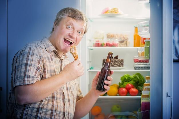 Hommes mûrs au réfrigérateur avec de la bière et de la cuisse de poulet