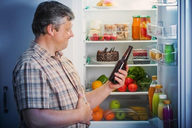 Hommes mûrs au réfrigérateur avec de la bière