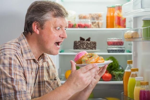 Hommes mûrs au réfrigérateur avec de la nourriture