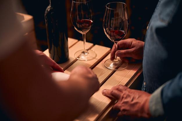 Hommes non reconnus debout près de la caisse en bois avec des verres de vin rouge dessus