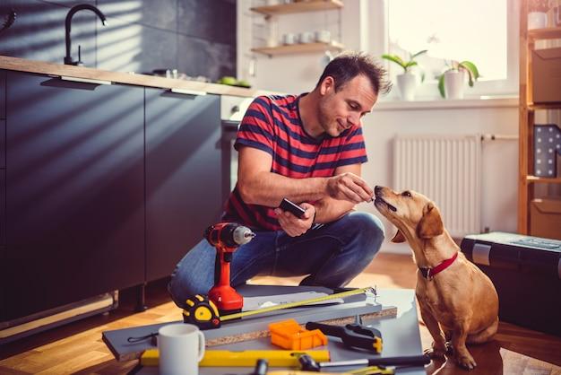 Hommes nourrissant son chien pendant la rénovation de la cuisine