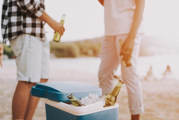 Les hommes ont de la bière à la fête sur la plage au coucher du soleil