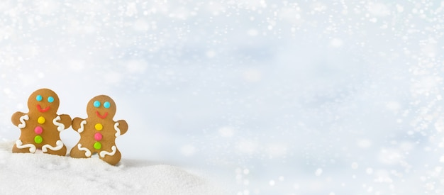 Les hommes de pain d'épice de noël se tiennent sur une montagne enneigée sur un fond blanc et des chutes de neige