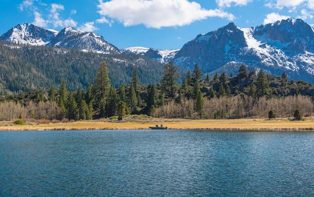 Hommes pêchant sur le bateau au bord du lac en californie
