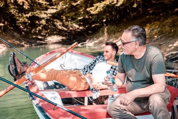 Hommes pêchant et se relaxant au bord du lac