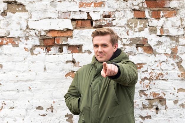 Hommes pointe sur quelque chose sur fond blanc. homme touchant un écran imaginaire, debout contre un vieux mur de briques blanches et rouges