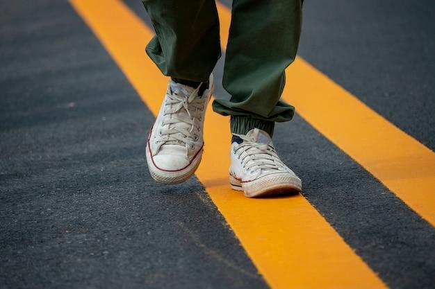 Hommes portant des baskets blanches marchant sur la route avec des lignes de circulation jaunes.