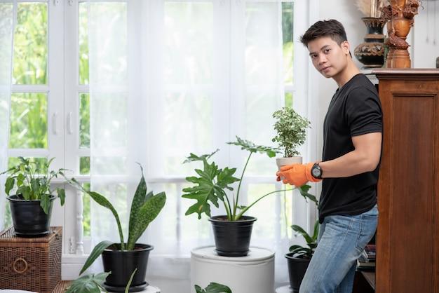 Des hommes portant des gants orange et plantant des arbres à l'intérieur.