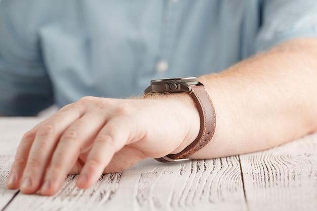 Hommes portant une montre noire avec bracelet en cuir noir sur fond blanc
