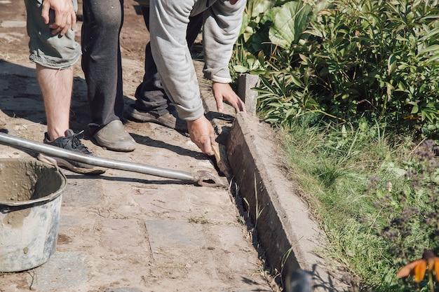 Les hommes posent des bordures pour le jointoiement d'un chemin de jardin, des travaux de construction sur un terrain de jardin.