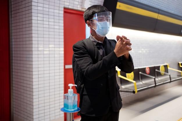 Les hommes qui travaillent en asie se lavent les mains avec du gel d'alcool dans le métro