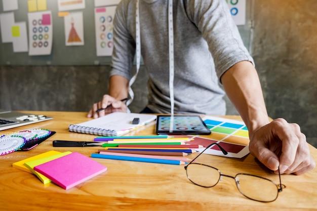 Les hommes qui travaillent comme créateurs de mode choisissent une carte de couleur pour les vêtements en tablette numérique au studio de travail.