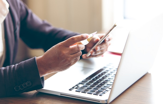 Les hommes qui utilisent des smartphones pour composer et envoyer envoient et reçoivent des e-mails lisent des messages et aident à acheter des produits en ligne sur le site web, événement de réseautage internet en ligne, plateforme de magasinage en ligne