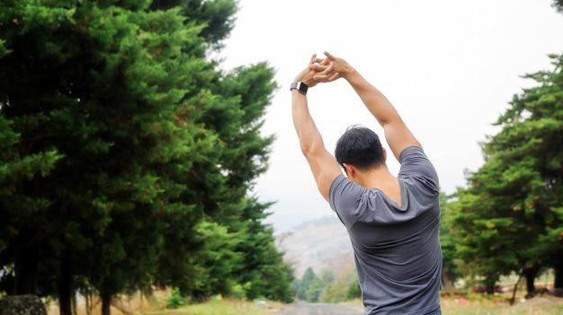 Les hommes réchauffent son corps préparer l'exercice le matin.