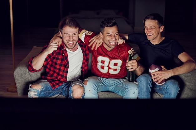 Hommes regardant la compétition de football américain