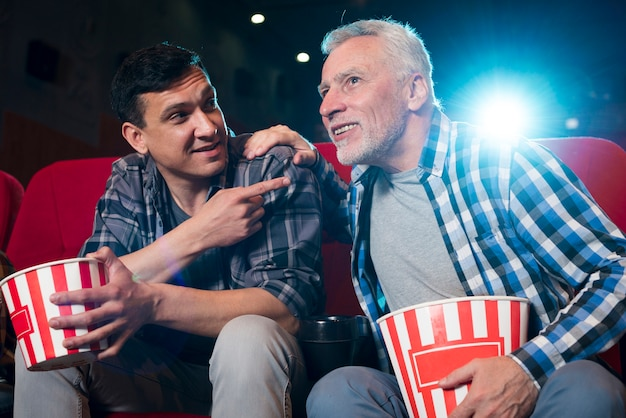 Hommes regardant un film au cinéma