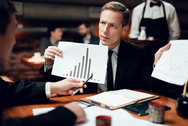 Les hommes regardent des graphiques et des tableaux