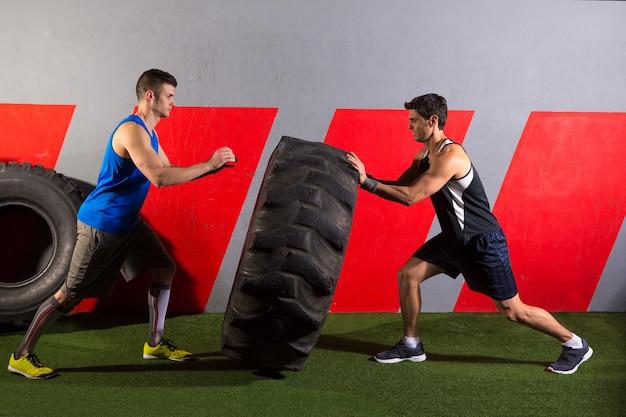 Hommes renversant un exercice de gymnase d'entraînement de pneu de tracteur