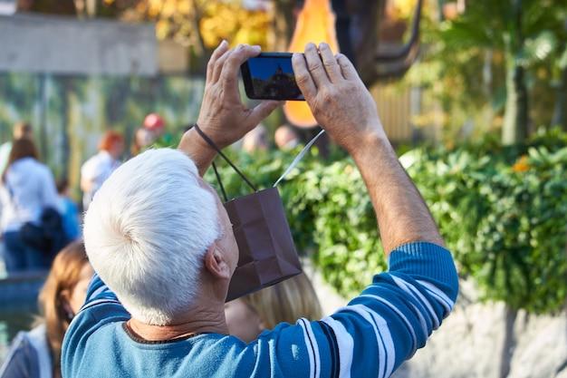 Hommes sur la rue photographiant avec un téléphone mobile, le fond est la ville estompée