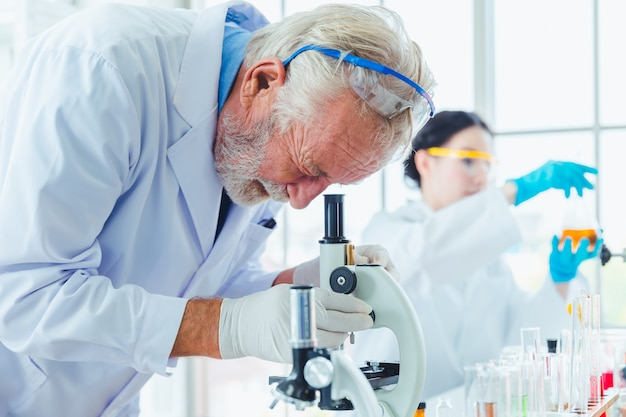 Des hommes scientifiques travaillant avec des produits chimiques microscopes en laboratoire