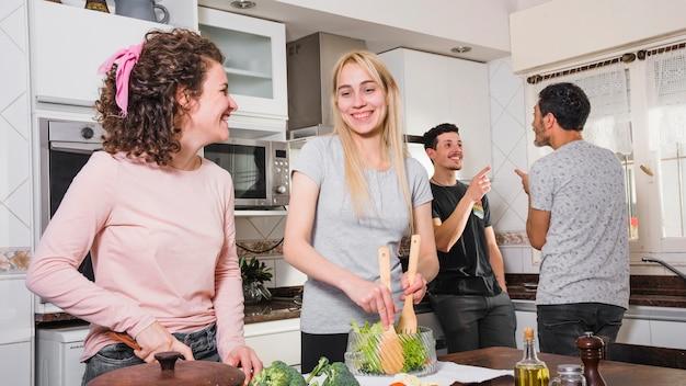 Des hommes se parlent et des femmes préparent une salade à table dans la cuisine