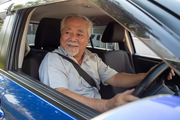 Hommes seniors asiatiques au volant d'une voiture et sourire joyeusement avec une expression positive heureuse pendant le trajet pour voyager, les gens aiment rire transport et détendu heureux homme mûr sur le concept de voyage sur la route