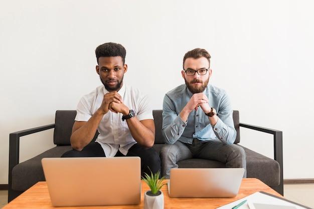 Hommes sérieux avec des ordinateurs portables