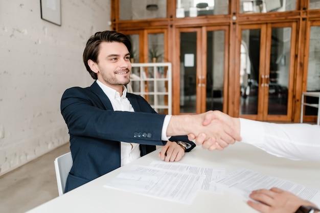 Les hommes serrant la main sur un accord et signer des papiers dans le bureau